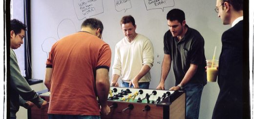 men playing foosball showing off positive work environment