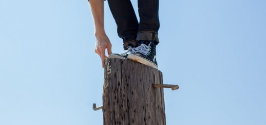 man in jeans and black shoes balancing on wooden post